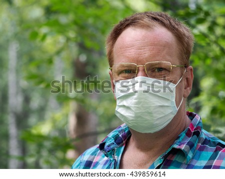 Portrait of a man with glasses and a medical mask. Background nature, a lot of greens - the grass, the trees. Concept - an allergy in the spring, summer. Summer's disease - an allergy, common cold - stock photo