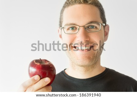 Portrait of a man with glasses holding an apple