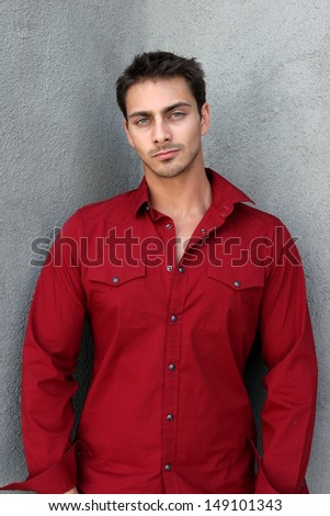 Portrait of a man with red shirt in fornt gray wall.