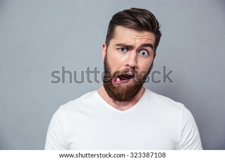Portrait of a man with stupid mug over gray background - stock photo