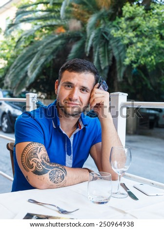 Portrait of a man with tattoo on his hand dressed in blue t shirt, sitting at a cafe table in exotic country.  - stock photo