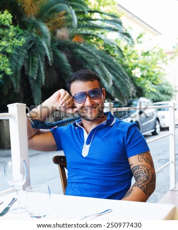 Portrait of a man with tattoo on his hand. Wearing sun glasses, dressed in blue t shirt, sitting at a cafe table in exotic country.  - stock photo