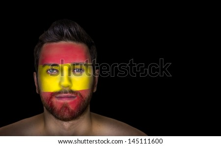 Portrait of a man with the flag of the Spain painted on his face - stock photo