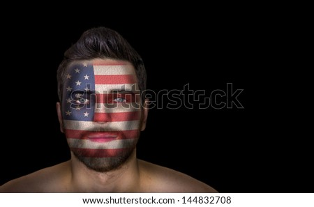 Portrait of a man with the flag of the USA painted on his face - stock photo