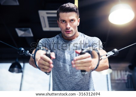Portrait of a man workout on fitness machine in gym - stock photo