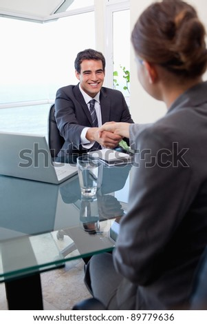 Portrait of a manager interviewing a female applicant in his office - stock photo