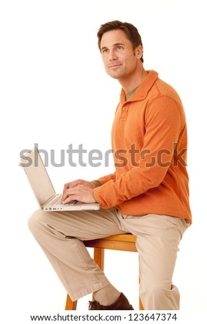 Portrait of a mature adult man wearing an orange sweater and khakis sitting on a stool working on a laptop computer looking up isolated on white