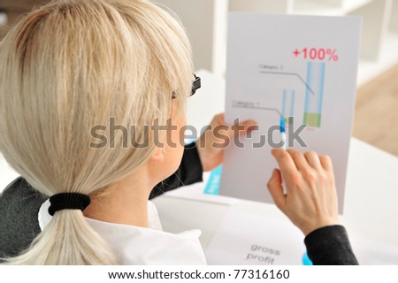 Portrait of a mature attractive business woman looking on her statistics - stock photo