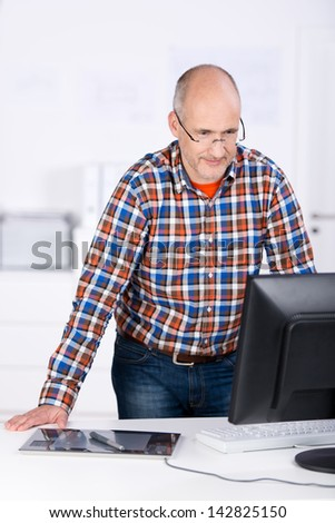 Portrait of a mature balding caucasian businessman, wearing glasses and casual clothing, standing behind an office desk and looking at the computer screen - stock photo