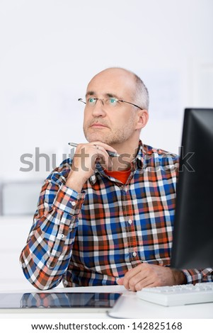 Portrait of a mature balding caucasian man wearing glasses, sitting at the office desk, holding his chin with the hand and looking up and away in a serious and pensive mood - stock photo