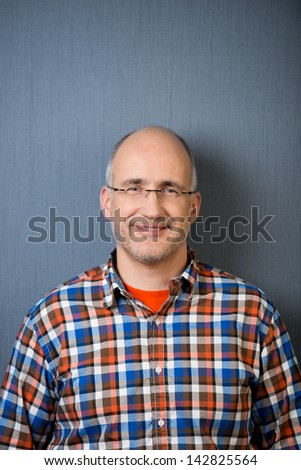 Portrait of a mature balding man with a friendly smile, wearing a casual clothing, in front of a gray wall