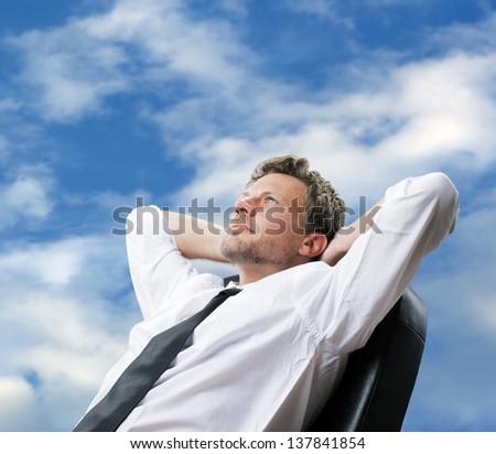 Portrait of a mature business man while relaxing with hands behind head - stock photo