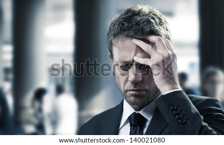 Portrait of a mature business man with headache - stock photo