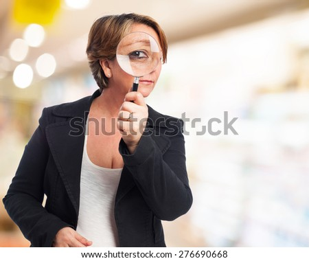 portrait of a mature business woman looking through a magnifying glass - stock photo