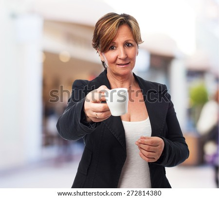portrait of a mature business woman offering a coffee cup - stock photo