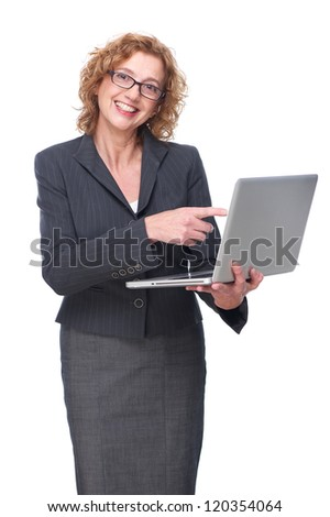 Portrait of a mature business woman smiling and pointing finger to laptop
