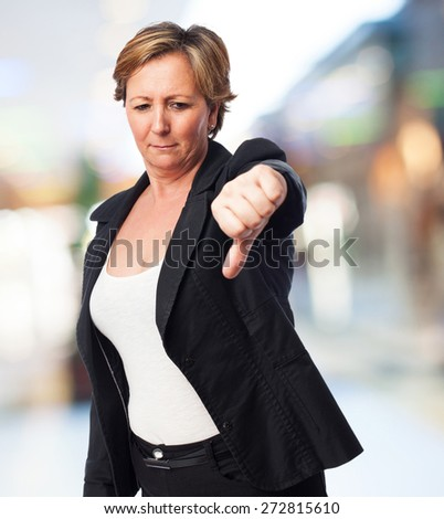 portrait of a mature business woman with thumb down - stock photo
