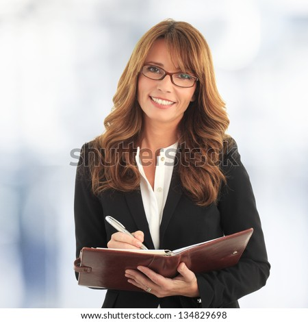 Portrait of a mature business woman writing in her notebook - stock photo