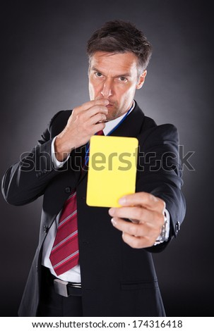 Portrait Of A Mature Businessman Showing Yellow Card Black Background - stock photo