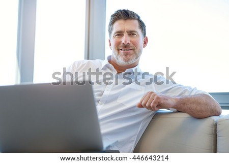 Portrait of a mature businessman sitting comfortably with a laptop computer on his lap, smiling positively at the camera - stock photo