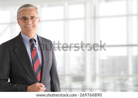 Portrait of a mature businessman standing in front of a large modern office window. The man is smiling and set ot the left side leaving room for copy. - stock photo