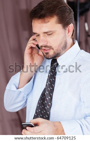 Portrait of a mature businessman talking on cellphone in office - stock photo