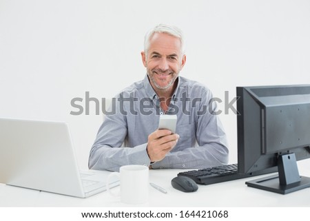 Portrait of a mature businessman with cellphone, laptop and computer at desk against white background - stock photo