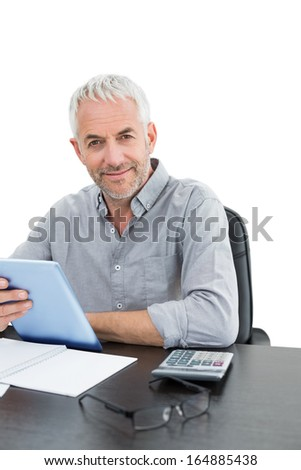 Portrait of a mature businessman with digital tablet and calculator at desk against white background