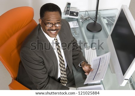 Portrait of a mature businessman with paperwork at computer desk - stock photo
