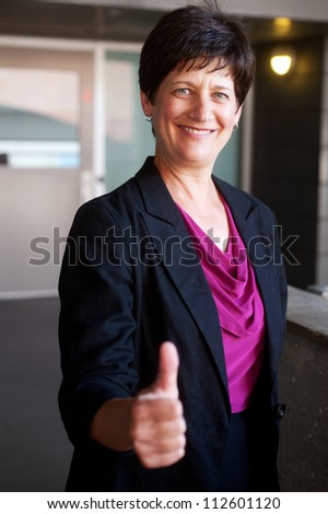 portrait of a mature businesswoman holding thumbs up outside office