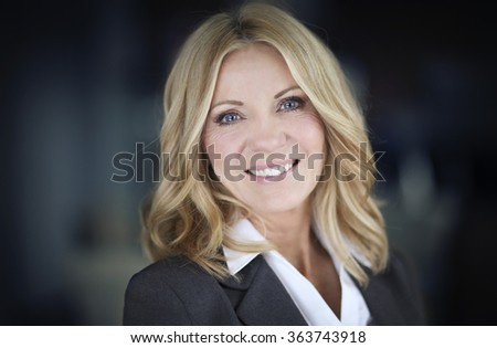 Portrait Of A Mature Businesswoman Smiling At The Camera - stock photo