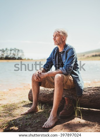 Portrait of a mature caucasian man sitting on a wooden log by a lake. Senior man relaxing at the lake and looking away at a view. - stock photo
