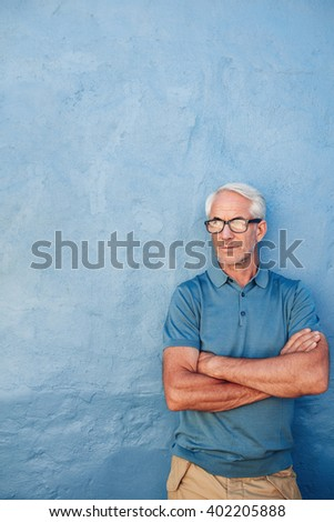 Portrait of a mature caucasian man with glasses standing with his arms crossed against blue background. Mid adult man looking away at copy space against a wall. - stock photo