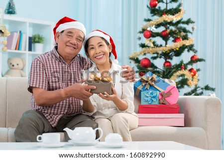 Portrait of a mature couple in Santa hats holding a giftbox