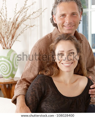 Portrait of a mature couple lounging on white sofa at home. - stock photo