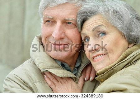 Portrait of a mature couple near wall on street