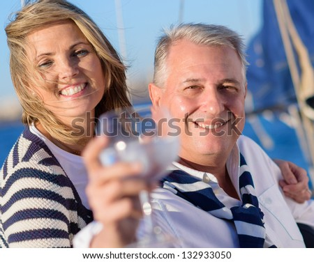 Portrait Of A Mature Couple Offering A Glass Of Wine - stock photo