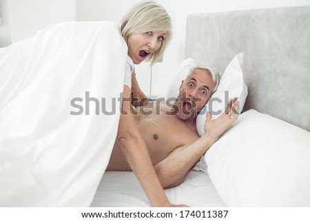 Portrait of a mature couple shouting in bed at home
