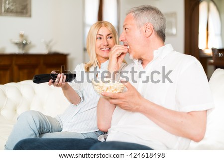 Portrait of a mature couple watching television - stock photo