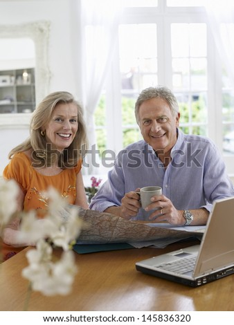 Portrait of a mature couple with map and laptop sitting at dining table in home - stock photo