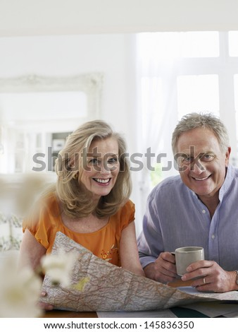 Portrait of a mature couple with map sitting at dining table in home - stock photo