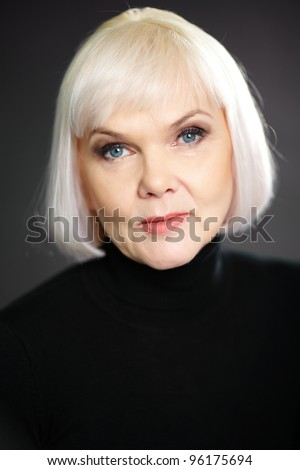 Portrait of a mature elegant lady looking at camera with a little smile - stock photo