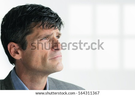 Portrait of a mature intelligent businessman looking up with lots of copy space