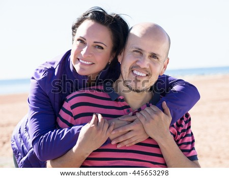 Portrait of a mature man and a woman happily embracing each other on the beach