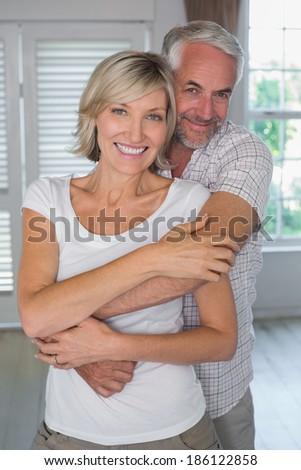 Portrait of a mature man embracing woman from behind at home
