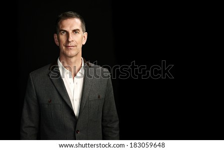 Portrait of a mature man on black background - stock photo
