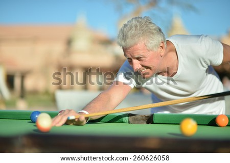 Portrait of a mature man Playing pool outdoor - stock photo