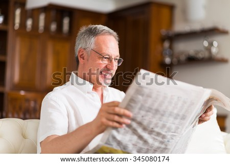 Portrait of a mature man reading a newspaper - stock photo