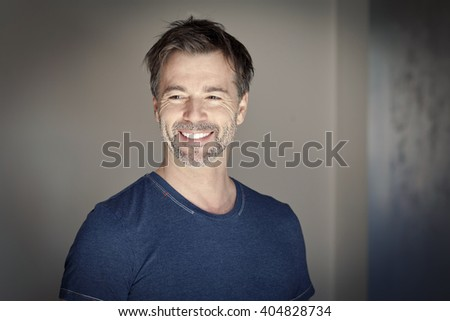 Portrait of a mature man smiling and looking away - stock photo