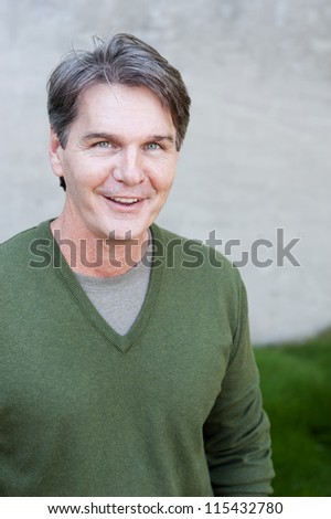 portrait of a mature man standing in a park - stock photo